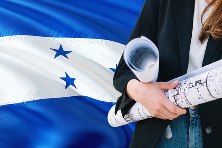 Honduran Architect woman holding blueprint against Honduras waving flag background. Construction and architecture concept.