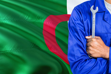 Algerian Mechanic in blue uniform is holding wrench against waving Algeria flag background. Crossed arms technician.
