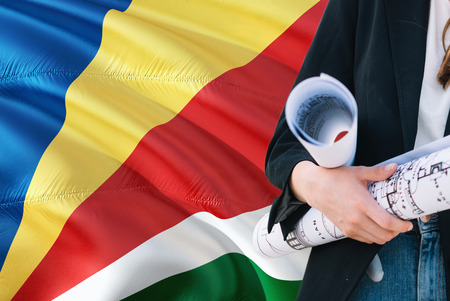 Seychellois Architect woman holding blueprint against Seychelles waving flag background. Construction and architecture concept.