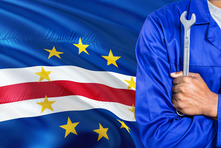 Mechanic in blue uniform is holding wrench against waving Cape Verde flag background. Crossed arms technician.