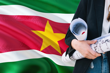 Surinamese Architect woman holding blueprint against Suriname waving flag background. Construction and architecture concept. Standard-Bild - 122649775