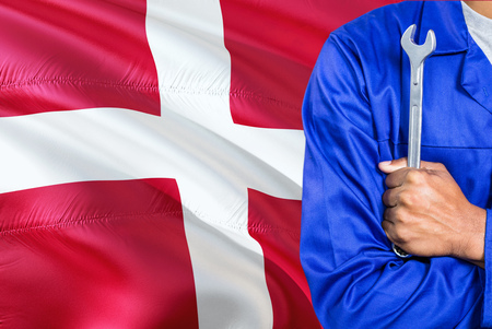 Danish Mechanic in blue uniform is holding wrench against waving Denmark flag background. Crossed arms technician. Foto de archivo