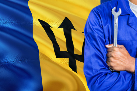 Barbadian Mechanic in blue uniform is holding wrench against waving Barbados flag background. Crossed arms technician. 스톡 콘텐츠