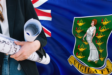 Architect woman holding blueprint against British Virgin Islands waving flag background. Construction and architecture concept.