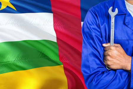 Mechanic in blue uniform is holding wrench against waving Central African Republic flag background. Crossed arms technician.