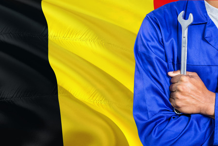 Belgian Mechanic in blue uniform is holding wrench against waving Belgium flag background. Crossed arms technician.