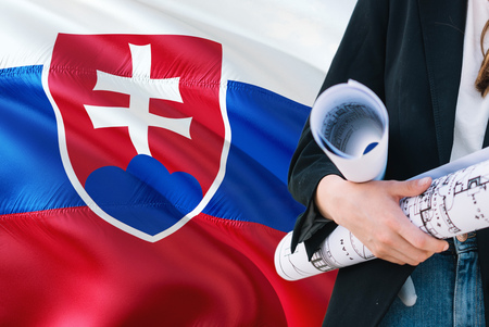 Slovak Architect woman holding blueprint against Slovakia waving flag background. Construction and architecture concept.