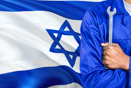 Israeli Mechanic in blue uniform is holding wrench against waving Israel flag background. Crossed arms technician. Banque d'images