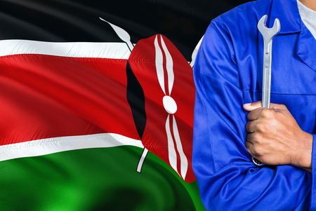 Kenyan Mechanic in blue uniform is holding wrench against waving Kenya flag background. Crossed arms technician.