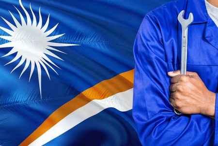 Mechanic in blue uniform is holding wrench against waving Marshall Islands flag background. Crossed arms technician.