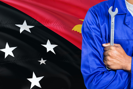 Mechanic in blue uniform is holding wrench against waving Papua New Guinea flag background. Crossed arms technician. Stock Photo