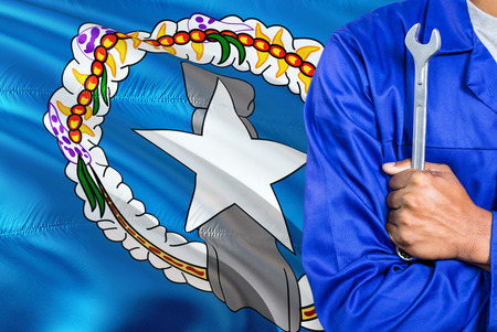 Mechanic in blue uniform is holding wrench against waving Northern Mariana Islands flag background. Crossed arms technician.