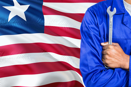 Liberian Mechanic in blue uniform is holding wrench against waving Liberia flag background. Crossed arms technician.