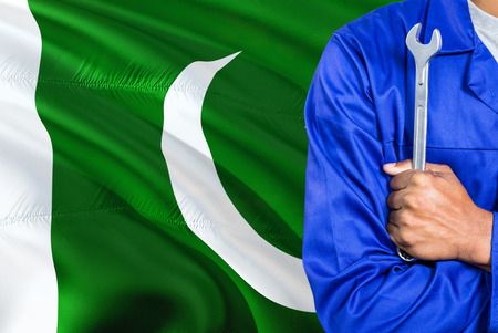 Pakistani Mechanic in blue uniform is holding wrench against waving Pakistan flag background. Crossed arms technician.