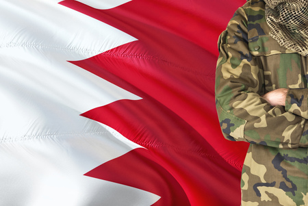 Crossed arms Bahraini soldier with national waving flag on background - Bahrain Military theme.