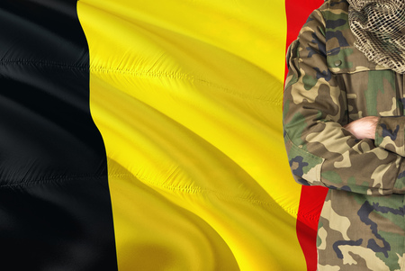 Crossed arms Belgian soldier with national waving flag on background - Belgium Military theme.