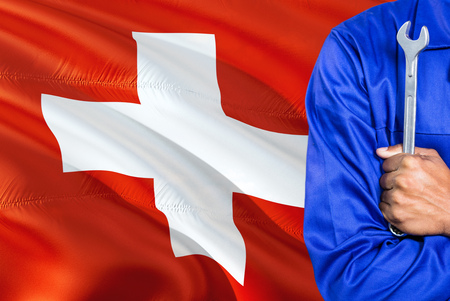 Swiss Mechanic in blue uniform is holding wrench against waving Switzerland flag background. Crossed arms technician.