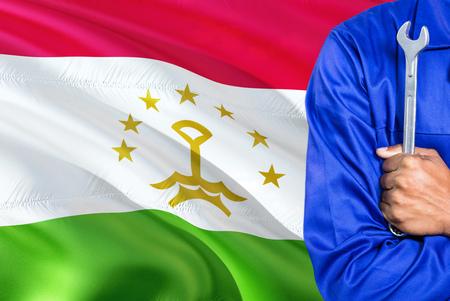 Tajik Mechanic in blue uniform is holding wrench against waving Tajikistan flag background. Crossed arms technician.