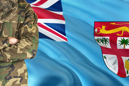 Crossed arms Fijian soldier with national waving flag on background - Fiji Military theme.