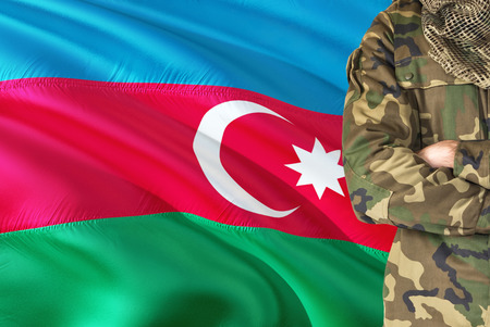 Crossed arms soldier with national waving flag on background - Azerbaijan Military theme.