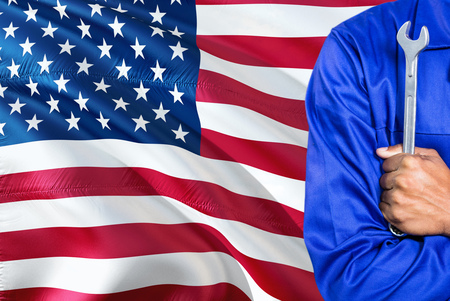 American Mechanic in blue uniform is holding wrench against waving United States of America flag background. Crossed arms technician. 版權商用圖片