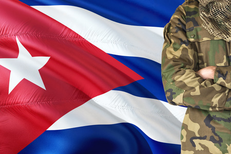 Crossed arms Cuban soldier with national waving flag on background - Cuba Military theme.