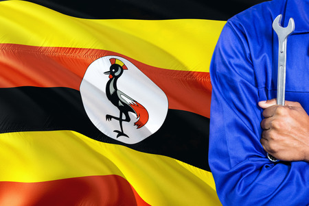 Ugandan Mechanic in blue uniform is holding wrench against waving Uganda flag background. Crossed arms technician. 版權商用圖片