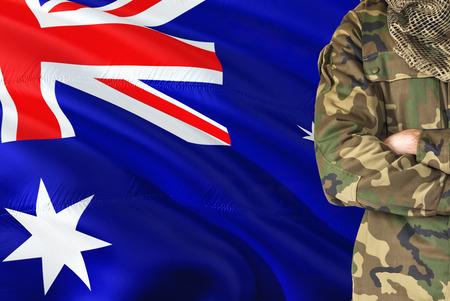Armi incrociate Soldato australiano con bandiera sventolante nazionale sullo sfondo - tema militare dell'Australia.