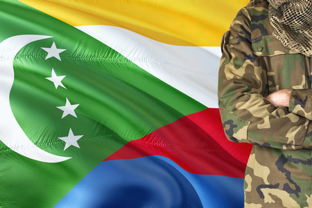 Crossed arms Comoran soldier with national waving flag on background - Comoros Military theme. Stock Photo