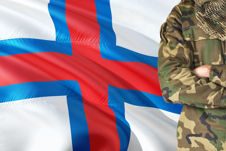 Crossed arms soldier with national waving flag on background - Faroe Islands Military theme.