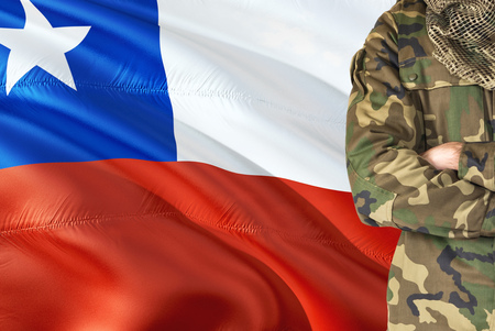 Crossed arms Chilean soldier with national waving flag on background - Chile Military theme.