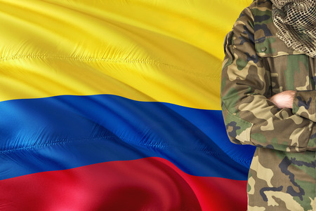Crossed arms Colombian soldier with national waving flag on background - Colombia Military theme.