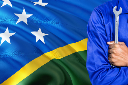 Mechanic in blue uniform is holding wrench against waving Solomon Islands flag background. Crossed arms technician.