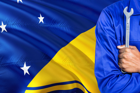 Mechanic in blue uniform is holding wrench against waving Tokelau flag background. Crossed arms technician.