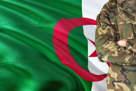 Crossed arms Algerian soldier with national waving flag on background - Algeria Military theme.