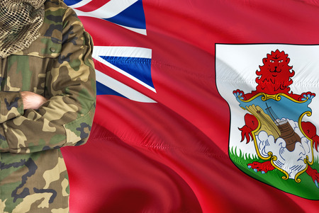 Crossed arms soldier with national waving flag on background - Bermuda Military theme.