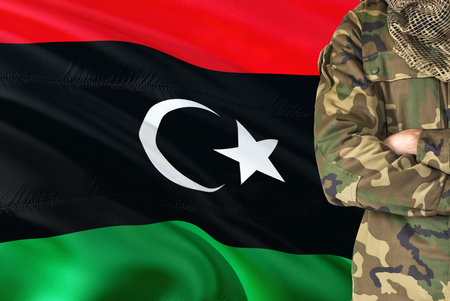 Crossed arms Libyan soldier with national waving flag on background - Libya Military theme.