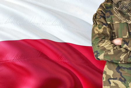 Crossed arms Polish soldier with national waving flag on background - Poland Military theme.