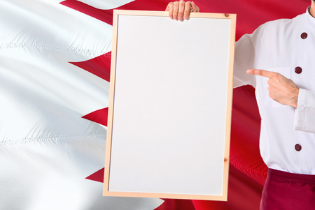 Bahraini Chef holding blank whiteboard menu on Bahrain flag background. Cook wearing uniform pointing space for text.