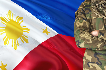 Crossed arms Filipino soldier with national waving flag on background - Philippines Military theme.