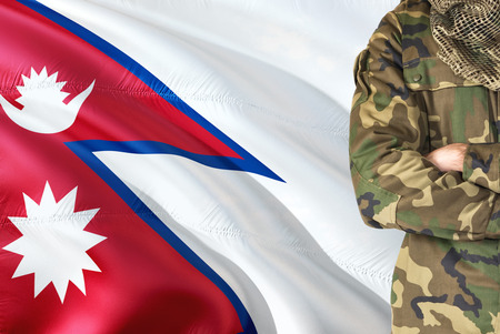 Crossed arms Nepalese soldier with national waving flag on background - Nepal Military theme. Фото со стока