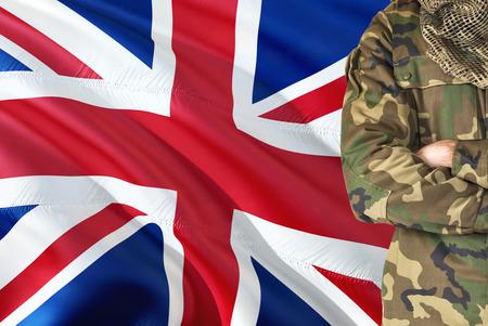 Soldado británico de brazos cruzados con la bandera nacional que agita en el fondo - tema militar del Reino Unido.