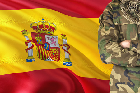 Crossed arms Spanish soldier with national waving flag on background - Spain Military theme. Stock fotó