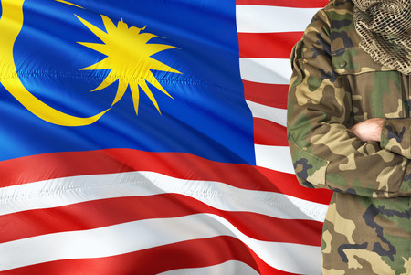 Crossed arms Malaysian soldier with national waving flag on background - Malaysia Military theme. Stock Photo