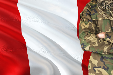 Crossed arms Peruvian soldier with national waving flag on background - Peru Military theme.