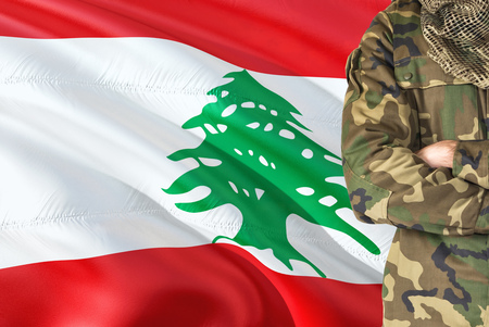 Crossed arms Lebanese soldier with national waving flag on background - Lebanon Military theme.