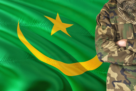 Crossed arms Mauritanian soldier with national waving flag on background - Mauritania Military theme. Stock Photo