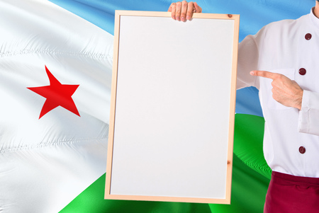 Chef holding blank whiteboard menu on Djibouti flag background. Cook wearing uniform pointing space for text.