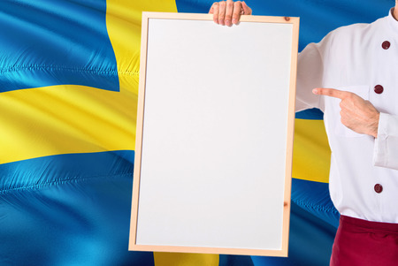 Swedish Chef holding blank whiteboard menu on Sweden flag background. Cook wearing uniform pointing space for text.