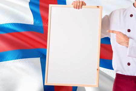 Chef holding blank whiteboard menu on Faroe Islands flag background. Cook wearing uniform pointing space for text.